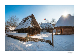 Sun warming up a traditional Romanian homestead in winter