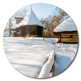 Snow cover in a Romanian Village with an old wooden church