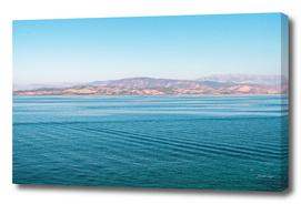 Blue ocean with mountain skyline under blue sky