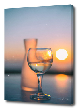 Bottle and glass of wine on table at sunset