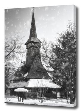 Traditional wooden Romanian Church seen through the Snowfall