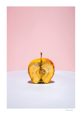 Old apple in a cut on a colored background