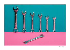 Seven wrenches on a colored background