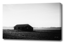 Old barn in misty farmland.