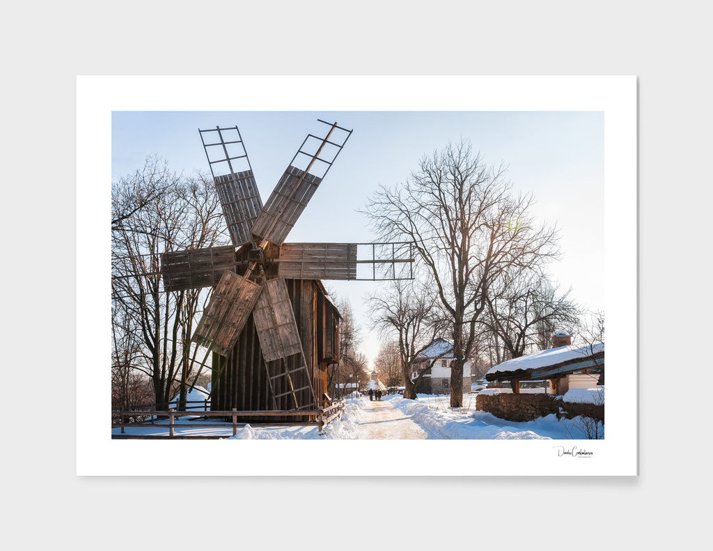 A traditional Romanian windmill on a snow covered street