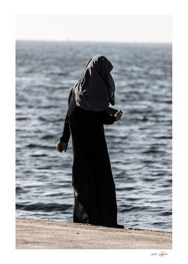 Young muslim girl walking at seaside