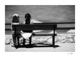 Two girls sitting near by near on a bench