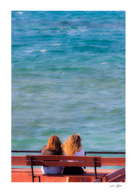 Two girls sitting on a bench at seaside
