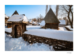 Traditional gate and a rural homestead covered in snow