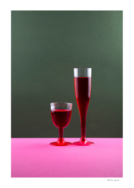 Two glasses with red wine on a colored background