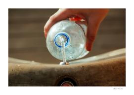 Female hand filling plastic water bottle