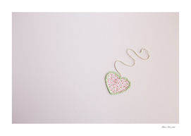 Heart-shaped cloth patch on white background