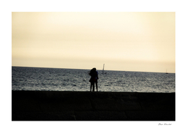 Silhouette of an embracing couple looking at the sea