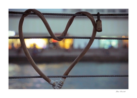 Heart-shaped padlock locked metal cables