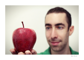 Man looking at red apple that placed on his hand