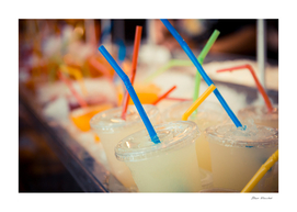 Selection of plastic cups with juice and colored straws