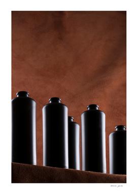Still Life with dark bottles on a brown background