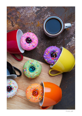 Colorful fancy donuts with black coffee