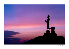 Silhouette of buddha statue with vivid sky