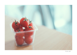 Red tomatoes in plastic container