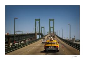 Yellow taxi on bridge