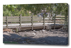 Rustic bridge with wooden fence over a dry stream near lake