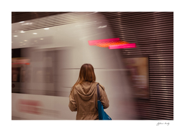 Rear View Of Young Woman Waiting For Subway. Blurred motion