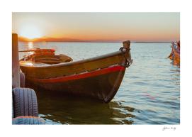 Sunset on the lake. Old lake fishing boat. Spain