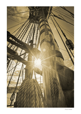 Bright sunlight shining through the rigging of a tall ship
