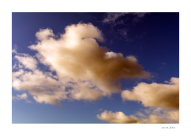 Dramatic Reddish Brown and white fluffy clouds in blue sky
