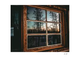 Grainy Sunset Reflection on Log Cabin Window