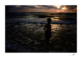 Young boy looking at the sunset