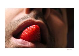 Sensual man eating a strawberry