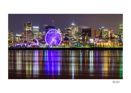 Illuminated ferris wheel by the river Montreal