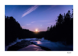 Moonrise over snow covered river