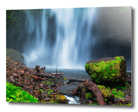 Green rock in front of a wide waterfall