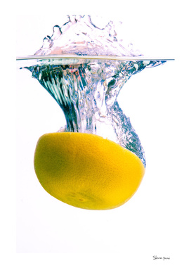 Grapefruit falls into water with big splash white background