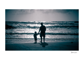 Father and Son on the beach at dusk