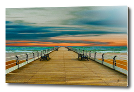 Wooden pier against the backdrop of a bright sunset.