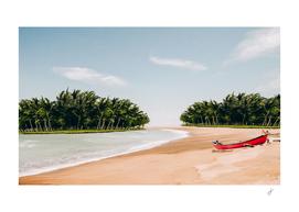 Red canoe on the coast of a tropical island.