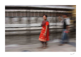 Nepalese girl at prayer wheels
