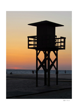 Lifeguard on the beach at sunset