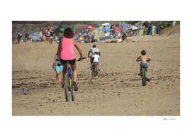 biking Family on the beach at Sea