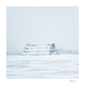Winter landscape with haystacks in field