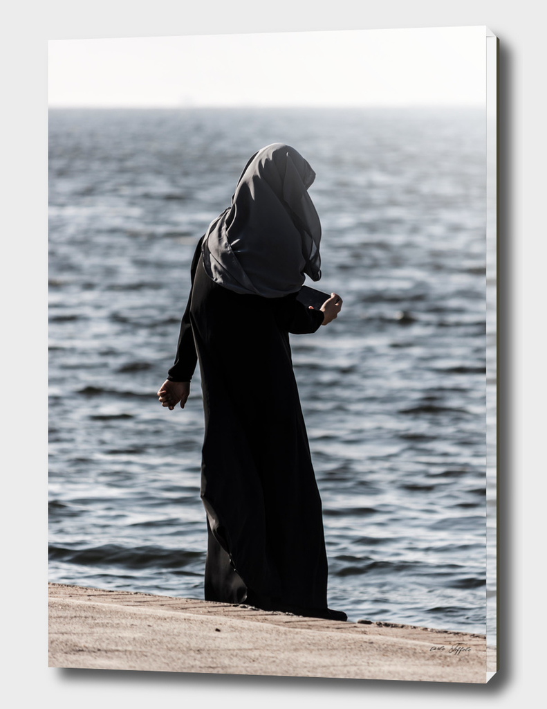 Young muslim girl walking at seaside