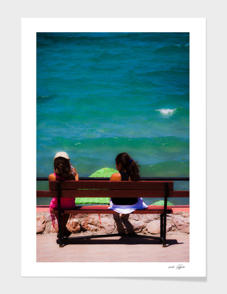 Two girls sitting on a bench at sea side