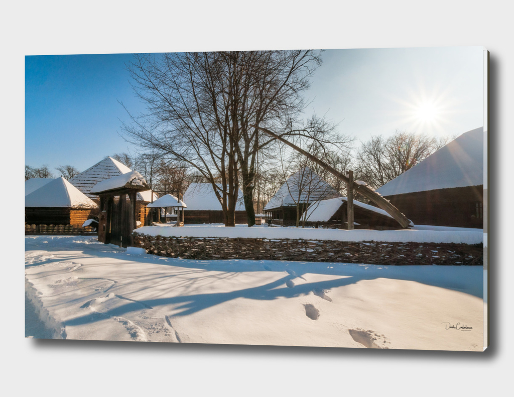 Sun shines over a traditional Romanian Village in winter