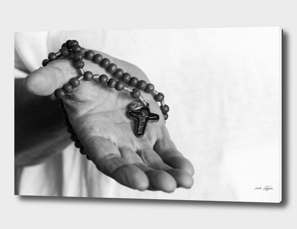 Hand of an old woman holds rosary while praying