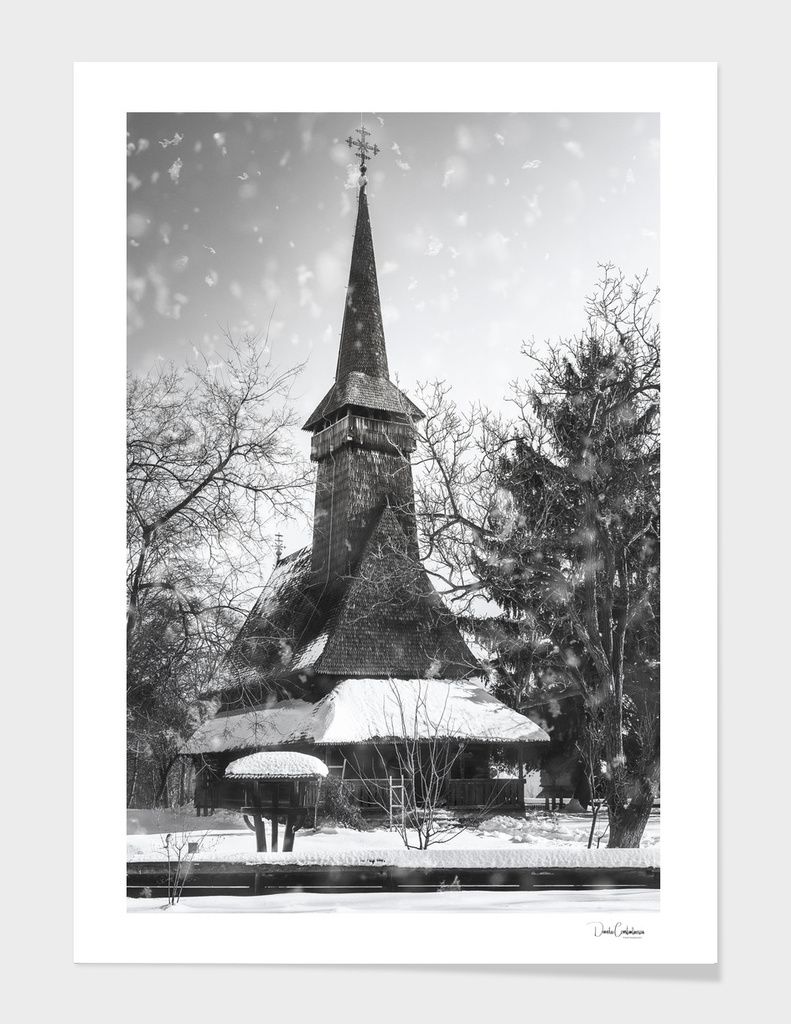 Traditional wooden Romanian Church seen through the Snowfall