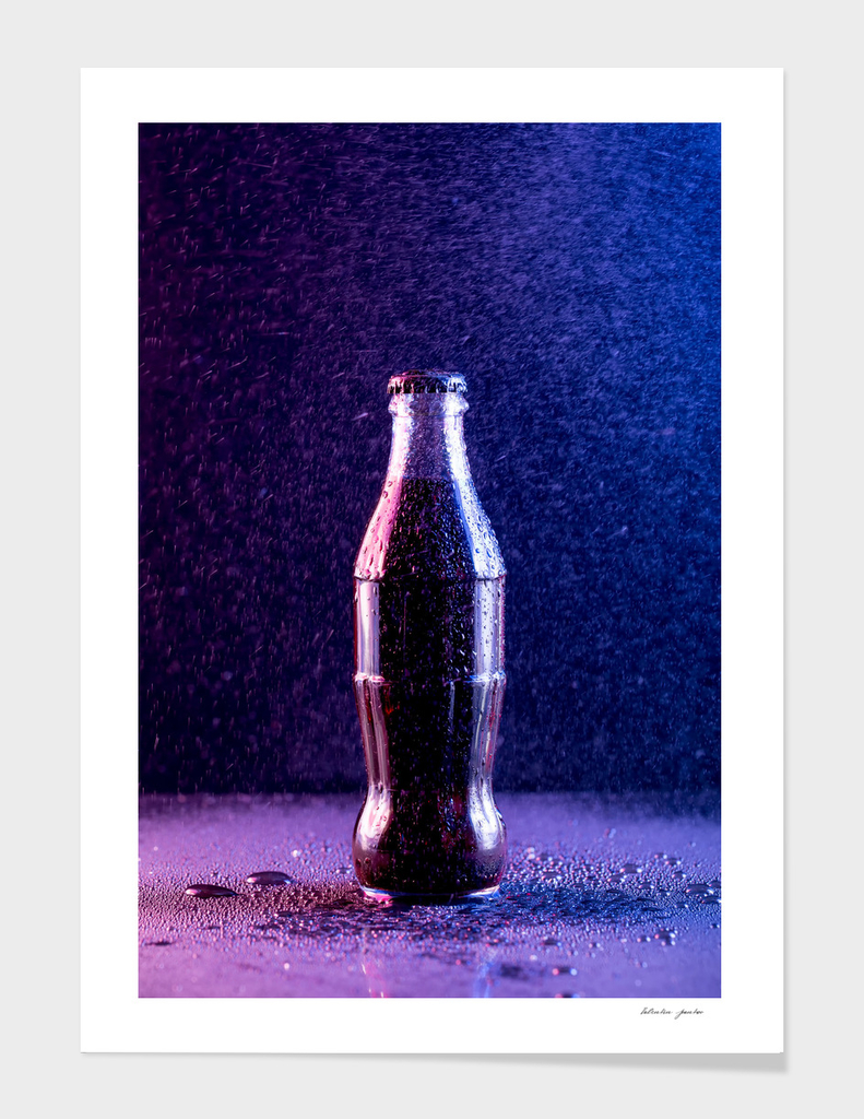 Glass bottle with carbonated drink under the drops of water